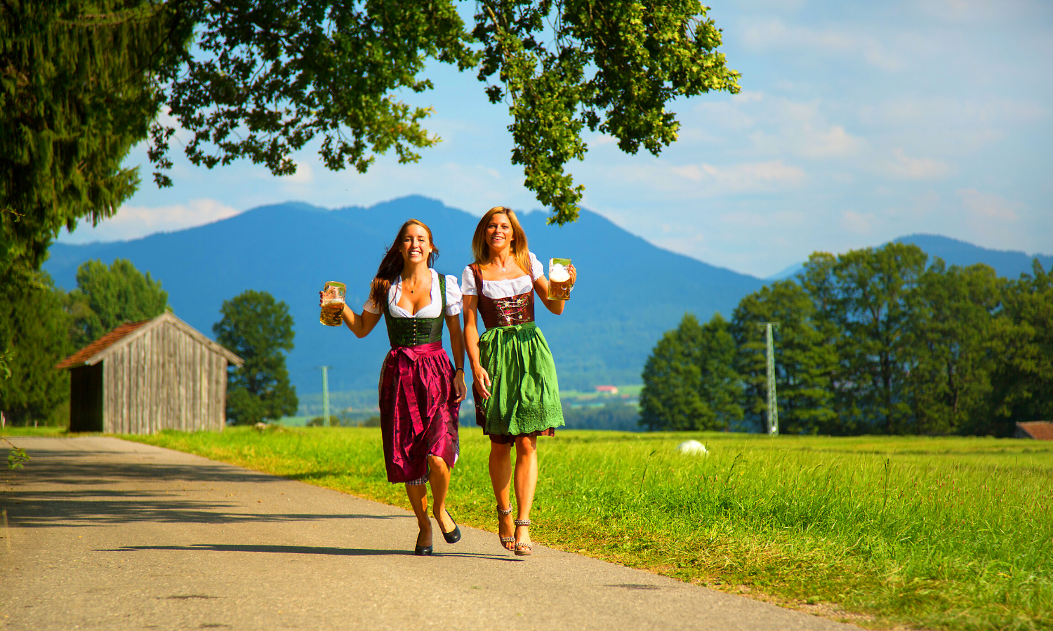Two women in traditional German dress holding steins of beer